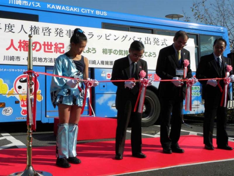2009年11月21日、川崎人権啓発活動地域ネットワーク協議会主催:ラッピングバス出発式にSAKADO WINDSが参加し、オープニングダンス、テープカット、花束の贈呈を行いました。